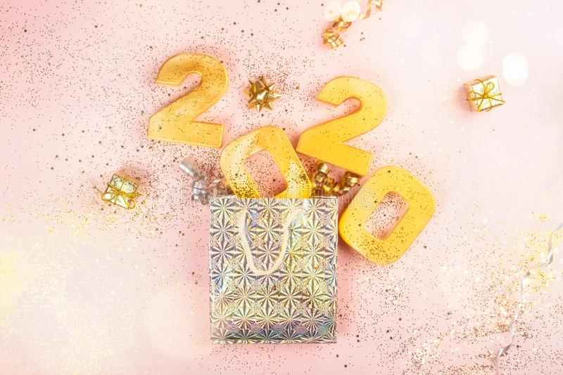 Happy New Year 2020. Digits 2020 are popping from the present bag. Holiday Party Decoration or postcard concept with top view and copy space stock photography