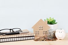 Wood house model, piggy bank, coins scattered from glass jar, notebooks, pen and eyeglasses on wooden background Royalty Free Stock Photography