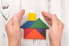 Hands surround a wooden house made by tangram home insurance concept Stock Photos